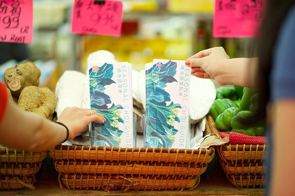 Two hands reaching for a Choi Guide at a supermarket