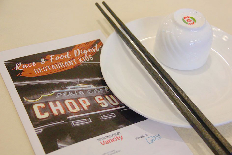 Event programme on table next to chopsticks resting on a saucer with a teacup