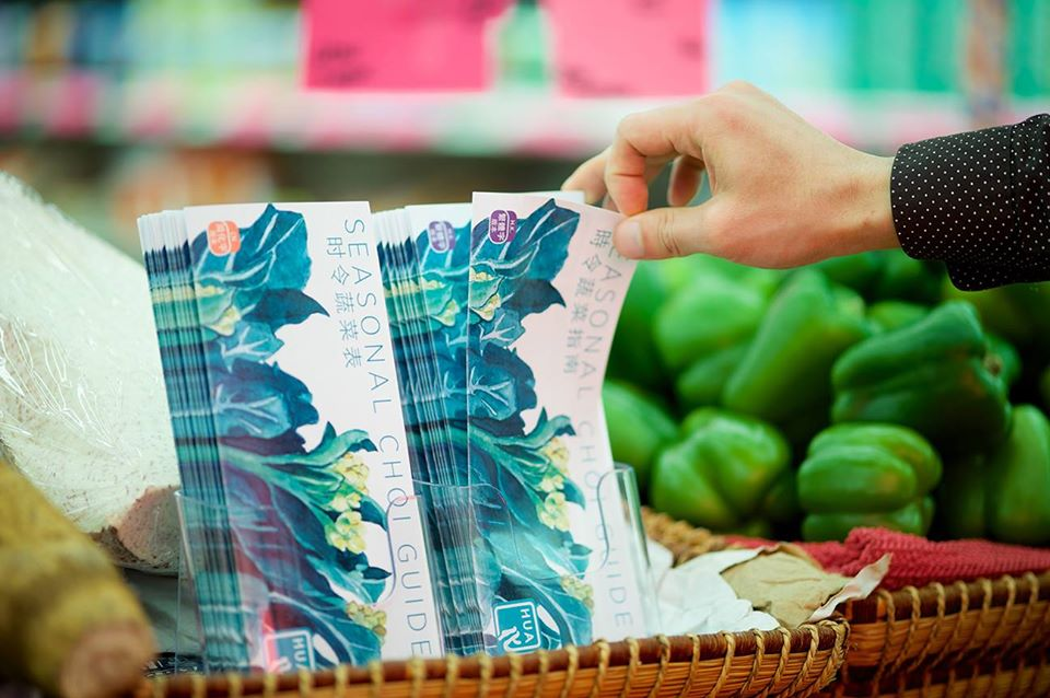 Person's hand picking up a Seasonal Choi Guide at a shop